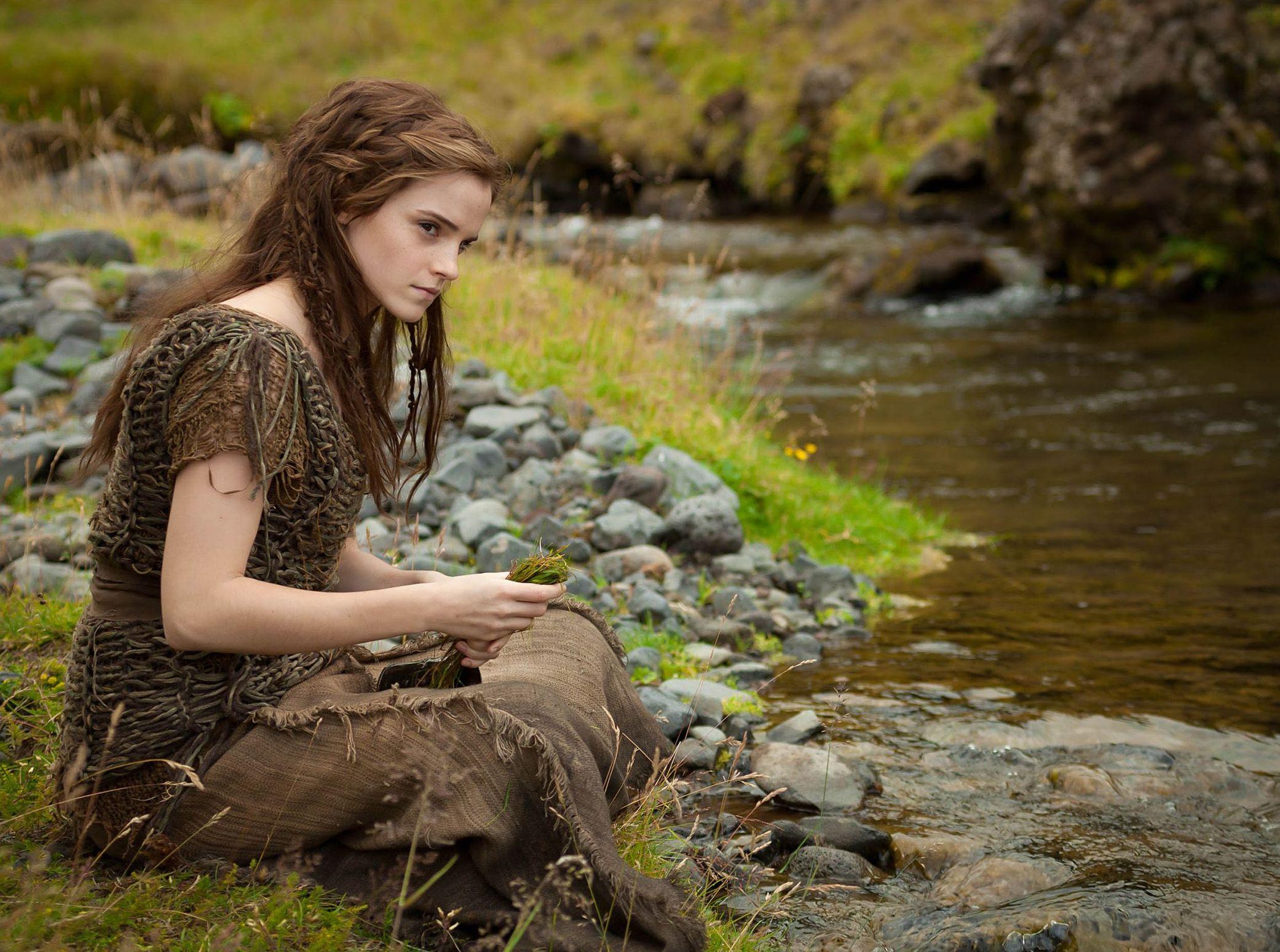 Emma Watson as Ila sitting by the water in Noah