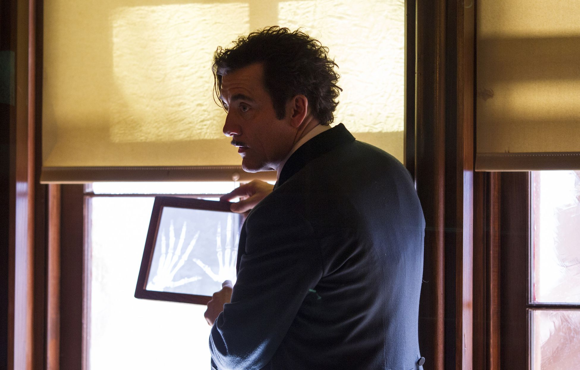 Clive Owen inspecting bones in The Knick