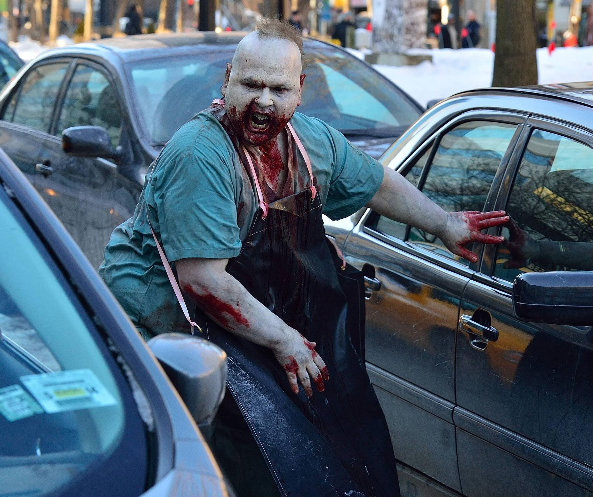 Fat vampire on the street in daylight between cars