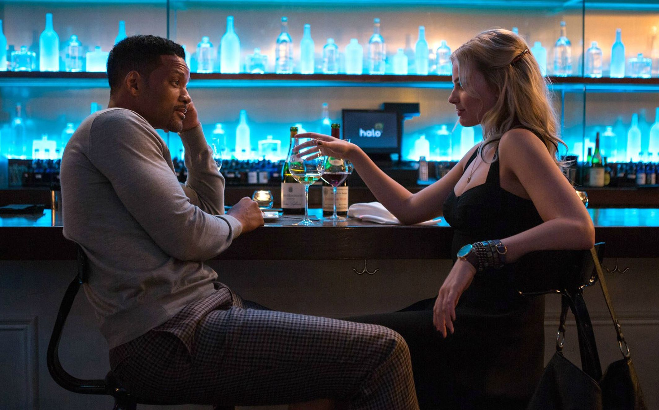 Will Smith as Nicky and Margot Robbie as Jess having a drink