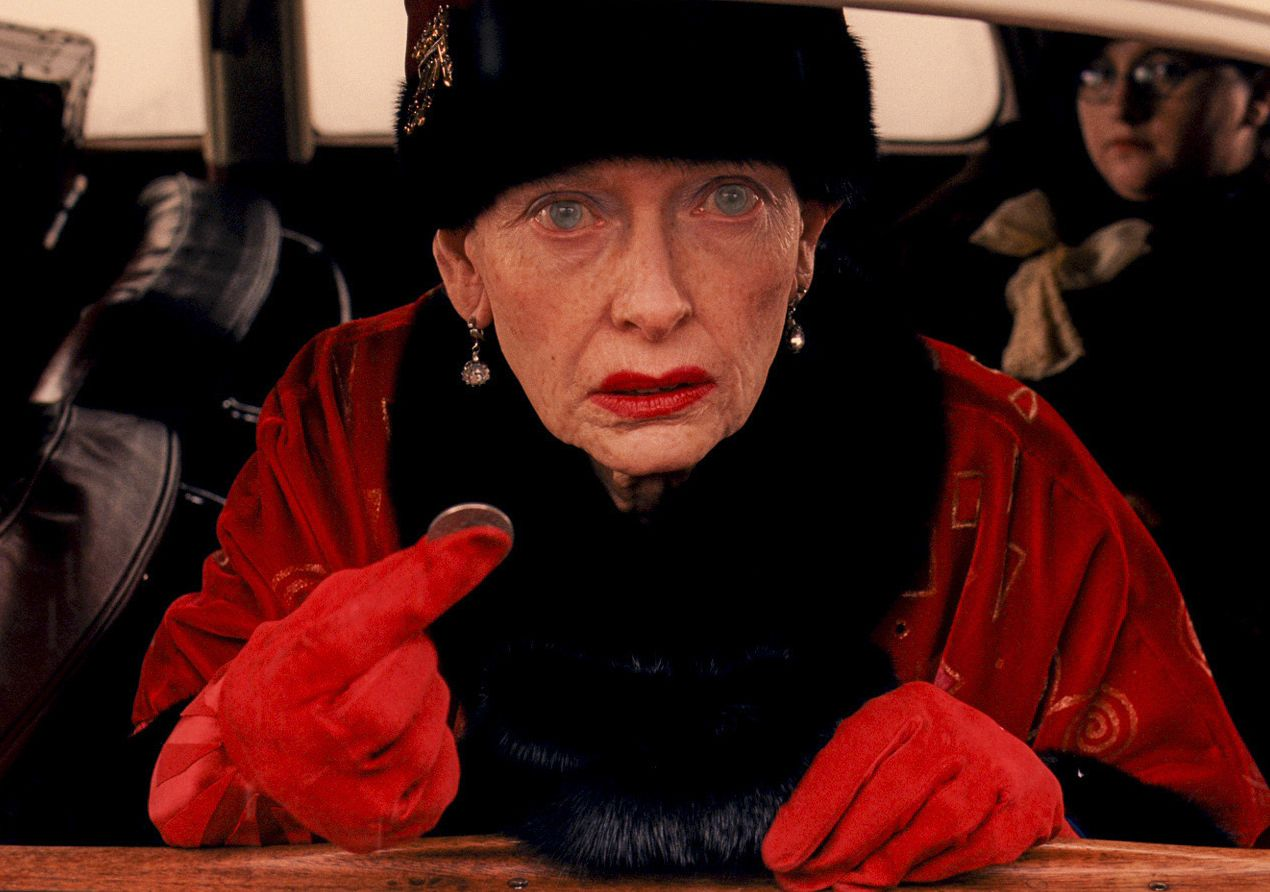 Old Tilda Swinton in red as Madame D. with coin