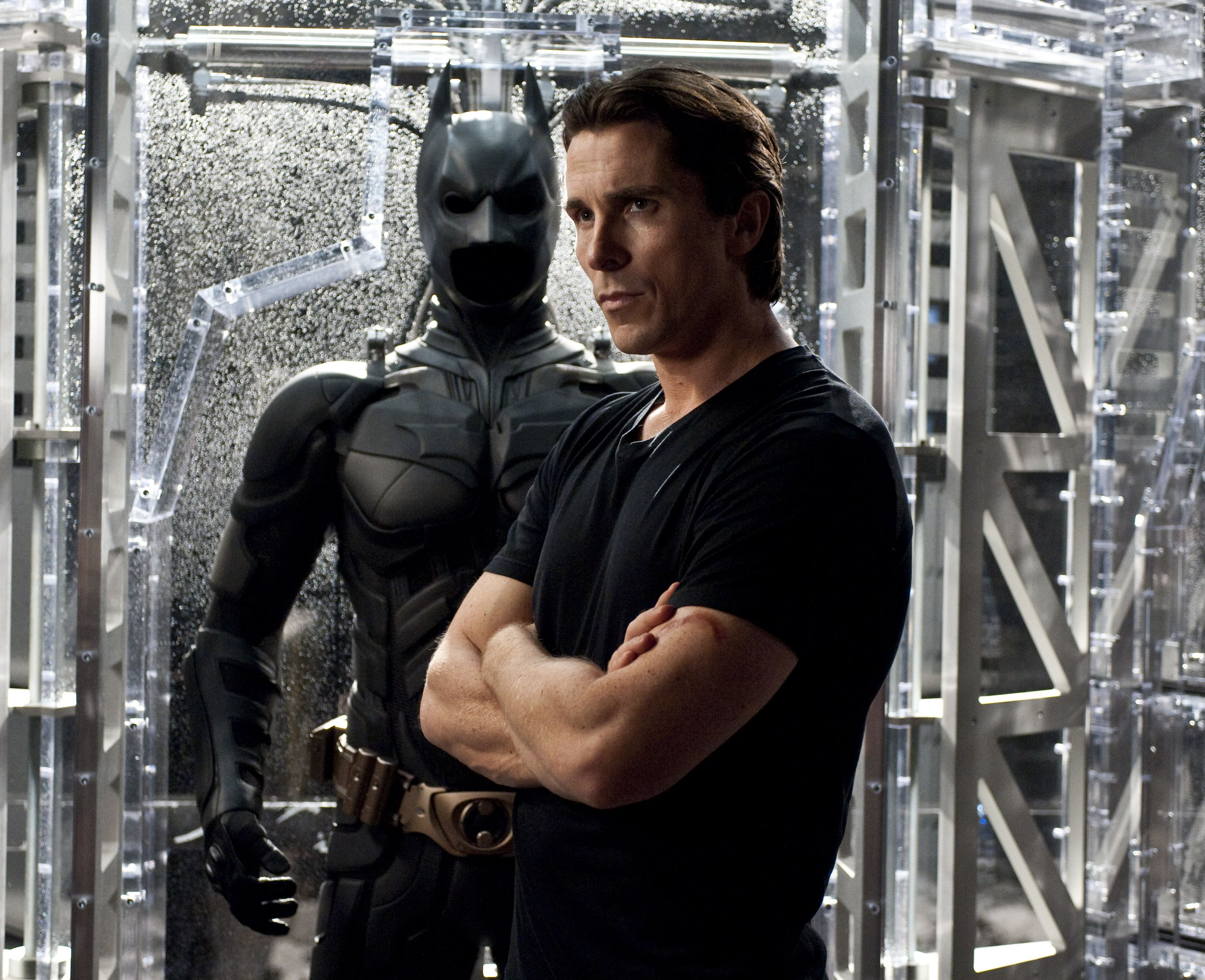Christian Bale as Bruce Wayne in front of Batsuit