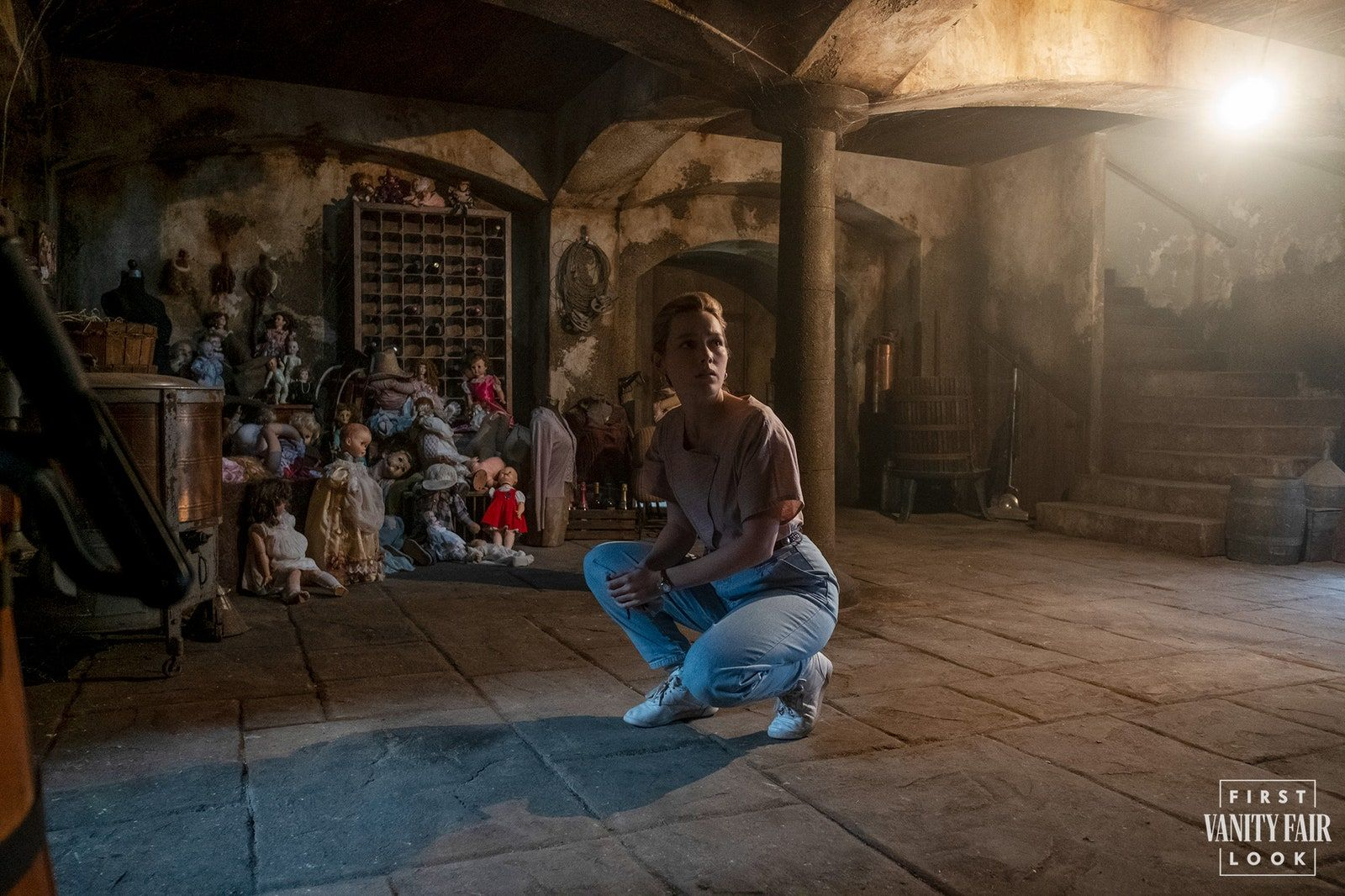 Victoria Pedretti as Dani Clayton, with abandoned toys in the basement from The Haunting of Bly Manor. (Look closely.) E